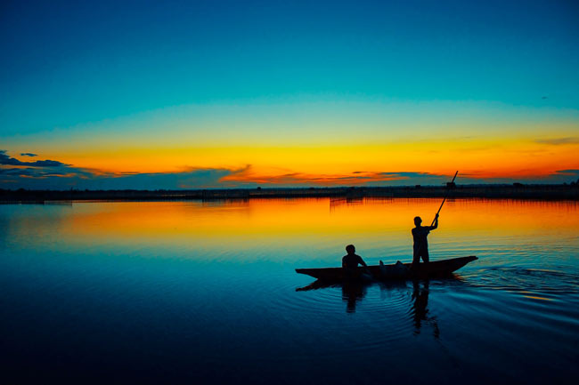 wooden boat with two men in sunset, live like you are dying